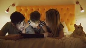 Famiglia felice con il piccolo figlio ed il gatto divertente che si trovano a letto a casa e che per mezzo del computer della com Fotografia Stock