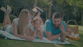 Famiglia felice con la figlia che riposa in natura video d archivio