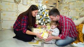Famiglia felice con la figlia del bambino che disimballa i regali di Natale a casa archivi video