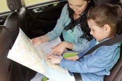 Famiglia felice con la mappa di viaggio che guida in automobile Fotografie Stock