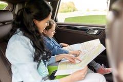 Famiglia felice con la mappa di viaggio che guida in automobile Immagine Stock