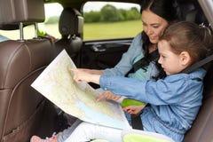 Famiglia felice con la mappa di viaggio che guida in automobile Immagine Stock Libera da Diritti