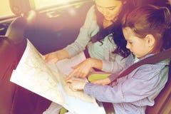 Famiglia felice con la mappa di viaggio che guida in automobile Fotografia Stock Libera da Diritti