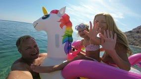 Famiglia felice con la ragazza che prende selfie nella disposizione dei posti a sedere del mare sull'unicorno gonfiabile stock footage