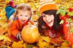 Famiglia felice con la zucca sulle foglie di autunno. Immagine Stock