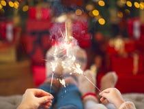 Famiglia felice con le luci di Bengala sopra i precedenti di Natale Fotografie Stock Libere da Diritti