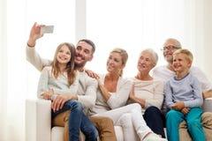 Famiglia felice con lo smartphone a casa Immagini Stock Libere da Diritti