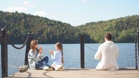 Famiglia felice con pesca della figlia nello stagno nella caduta stock footage