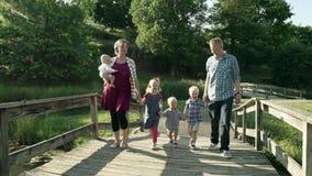 Famiglia felice con quattro bambini che camminano sul ponte in parco HD pieno video d archivio