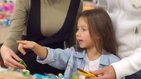 Famiglia felice con una caramella ed i dolci di acquisto del bambino nel supermercato Primo piano stock footage