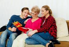 Famiglia felice - coppia con la donna anziana che contenitore di regalo della tenuta e scarpa di bambino Immagini Stock