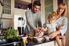 Famiglia felice in cucina che produce prima colazione immagini stock libere da diritti