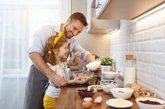 Famiglia felice in cucina La figlia del bambino e del padre impasta la pasta a fotografia stock libera da diritti