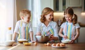 Famiglia felice in cucina la madre ed i bambini che preparano la pasta, cuociono i biscotti fotografia stock libera da diritti