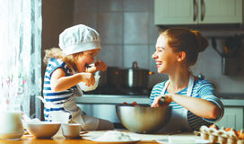 Famiglia felice in cucina la madre ed il bambino che preparano la pasta, cuociono
