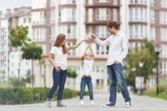 Famiglia felice davanti alla nuova costruzione di appartamento Fotografia Stock Libera da Diritti