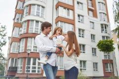 Famiglia felice davanti alla nuova costruzione di appartamento Immagini Stock