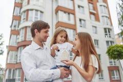 Famiglia felice davanti alla nuova costruzione di appartamento Fotografia Stock