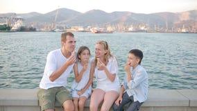 Famiglia felice del gioco che mangia il gelato Giorno pieno di sole caldo stock footage