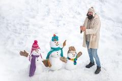 : Famiglia felice del pupazzo di neve di inverno Neve-donna della madre, neve-uomo del padre e fotografie stock