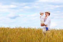 Famiglia felice dell'agricoltore sul giacimento di grano Immagine Stock Libera da Diritti
