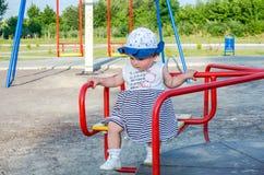 Famiglia felice della giovane neonata che giocano sull'oscillazione e giro nel sorridere del parco di divertimenti Immagini Stock Libere da Diritti