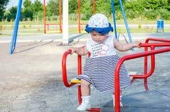 Famiglia felice della giovane neonata che giocano sull'oscillazione e giro nel sorridere del parco di divertimenti Immagine Stock