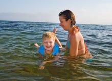 Famiglia felice della madre con il bambino nelle onde sul mare Fotografie Stock Libere da Diritti