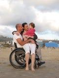 Famiglia felice della sedia a rotelle immagine stock