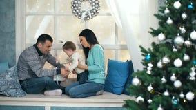Famiglia felice di bello natale con la bambina in maglioni tricottati che si siedono sul davanzale stock footage