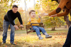 Famiglia felice divertendosi su un giro dell'oscillazione ad un giardino un il giorno di autunno Fotografia Stock Libera da Diritti
