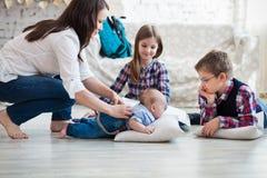 Famiglia felice divertendosi sul pavimento nel salone Fotografia Stock Libera da Diritti