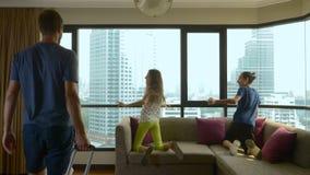 Famiglia felice, donna, uomo e due bambini con una valigia sui precedenti dei grattacieli in una finestra panoramica stock footage