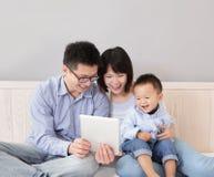 Famiglia felice facendo uso del pc della compressa Fotografie Stock Libere da Diritti