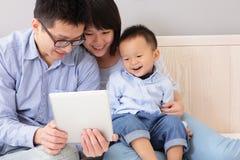 Famiglia felice facendo uso del pc della compressa Fotografia Stock Libera da Diritti
