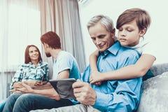 Famiglia felice facendo uso del PC della compressa insieme a casa fotografia stock libera da diritti