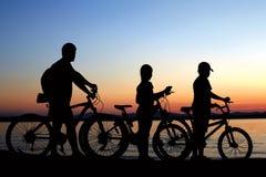 Famiglia felice - generi con due bambini sulle bici con il cane immagine stock