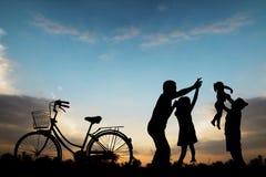 Famiglia felice, gioco del padre e madre con la figlia nell'insieme del sole Immagine Stock Libera da Diritti