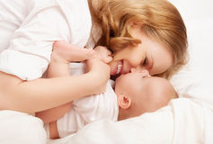 Famiglia felice. il bambino e la madre giocano, baciano, solleticano, ridono a letto Fotografia Stock