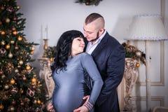 Famiglia felice Il marito abbraccia amoroso la sua moglie incinta sui precedenti dell'albero di Natale e del camino fotografie stock
