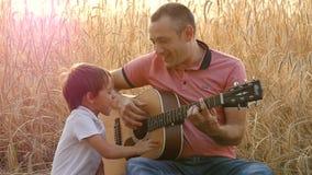 Famiglia felice: il padre ed il suo piccolo figlio sono riposare, sedentesi in un giacimento di grano Un uomo e un gioco da bambi stock footage