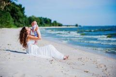 Famiglia felice La giovane madre getta sul bambino nel cielo, il giorno soleggiato sulla spiaggia Fotografie Stock Libere da Diritti