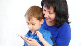 Famiglia felice: La mamma ed il figlio tengono uno smartphone e giocano con la domanda di bambini in Internet La generazione stock footage