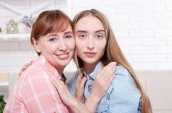 Famiglia felice Le macro donne affronta a casa il fondo Madre e figlia Giorno di madri E Fotografie Stock