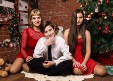 Famiglia felice, madre con due bambini accanto all'albero di cristmas nel giorno di Natale immagini stock libere da diritti