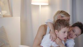 Famiglia felice - madre con due figli che abbracciano a letto archivi video