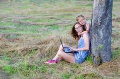 Famiglia felice: madre e figlia che lavorano ad un computer portatile in natura, Fotografie Stock Libere da Diritti
