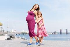 Famiglia felice, madre incinta e suo il bambino della bambina della figlia camminanti ed abbraccianti sull'argine nel giorno di e Immagini Stock Libere da Diritti