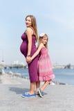 Famiglia felice, madre incinta e suo il bambino della bambina della figlia camminanti ed abbraccianti sull'argine nel giorno di e Fotografie Stock Libere da Diritti