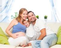 Famiglia felice madre, padre e figlia incinti del bambino a hom Immagine Stock